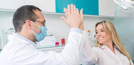 Smiling dental patient gives doctor high five