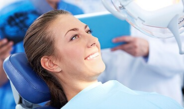 Young female patient smiling in dental chair