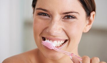 Happy woman brushing teeth