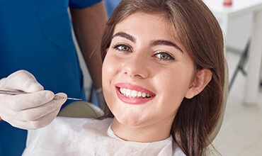 Smiling young female patient in dental chair