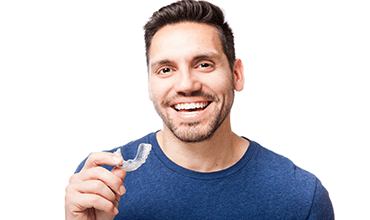 Smiling man holding Invisalign tray