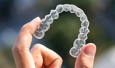 A hand holding up a clear aligner for a patient in need of Invisalign in Chevy Chase
