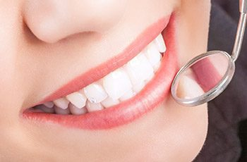 Closeup beautiful smile with dental mirror