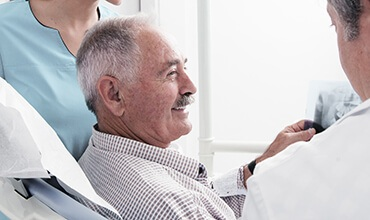 Older male patient smiling at dentist