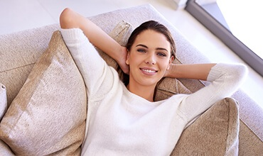 Woman resting on couch with hands behind head