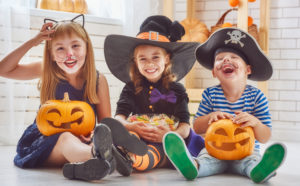 Halloween kids in costume candy and pumpkins