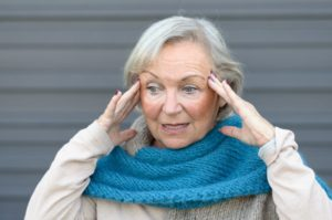 older woman confused holding head