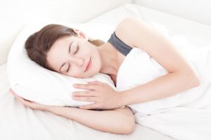 woman smiling while sleeping peacefully