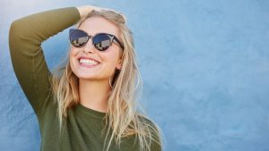 woman in sunglasses smiling with veneers in Chevy Chase
