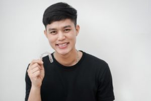young man holding an aligner for Invisalign in Chevy Chase