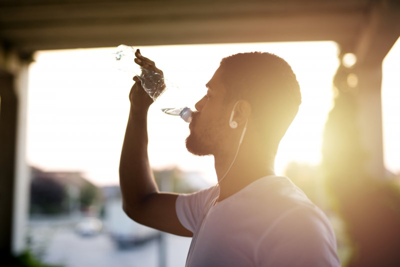athlete drinking water after exercising
